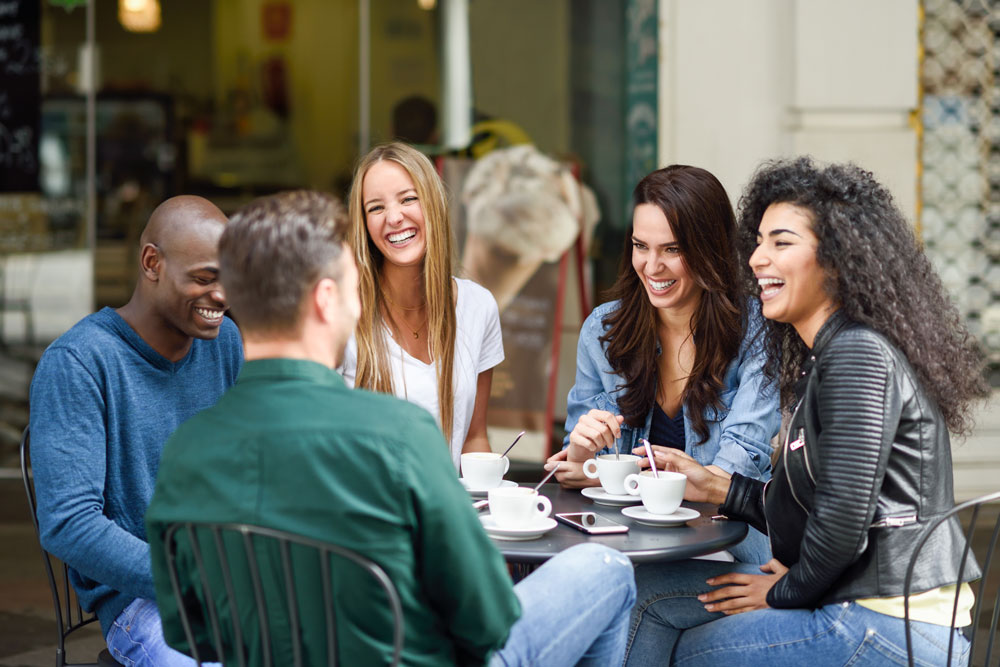 People smiling at a coffeeshop table